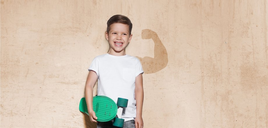 Skater boy in white T-shirt, concrete wall on background
